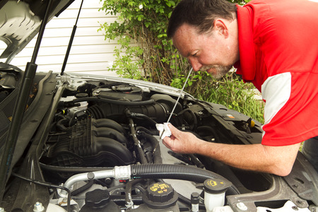 A mechanic checking the oil level of a newer car. Stock Photo