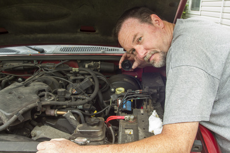 A mechanic checking the brake fluid levels in a older vehicle.