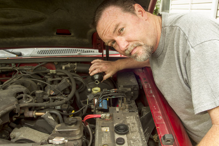 mileage: A mechanic pouring brake fluid in a master cylinder of a high mileage vehicle.