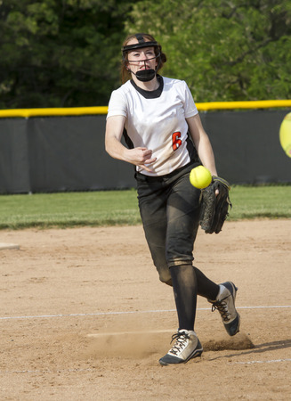 A fastpitch softball pitcher brings it during a game.
