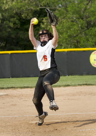 A fastpitch softball pitcher brings the heat during a high school game. Foto de archivo