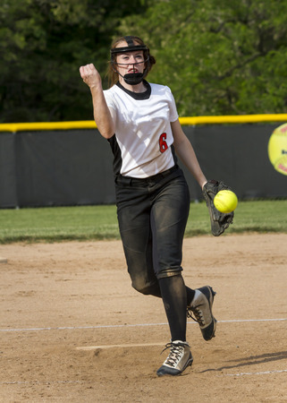 fastpitch: A high school fastpitch softball player brings the heat during a game. Stock Photo