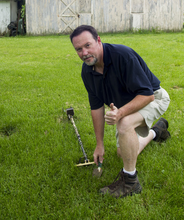 detecting: A man metal detecting in a old farm house backyard. Stock Photo