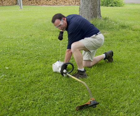 trimmer: A man trying to start a string trimmer.