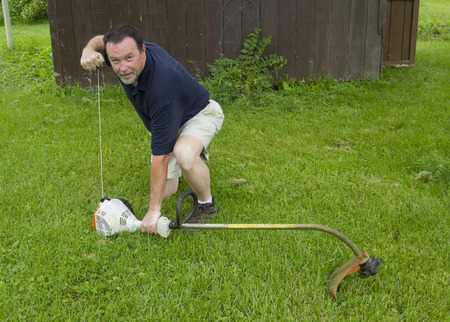 A man strting his gas powered srting trimmer.