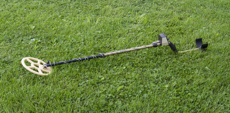 metal detector: A metal dector laying in the grass ready to be used.