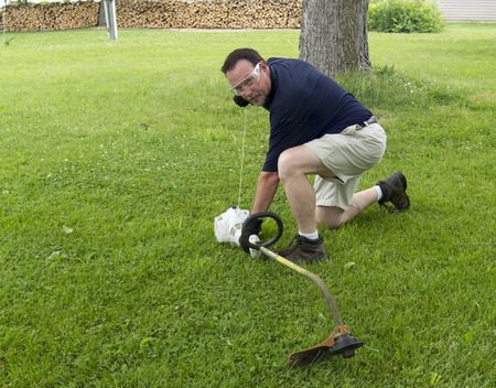 eater: A man starting a gasoline powered weed eater.