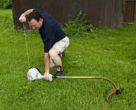 gasoline powered: A man starting a gasoline powered gas trimmer.