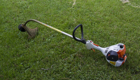 A gasoline powered string trimmer in the grass ready to be used.