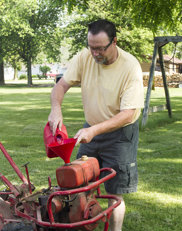 tines: Putting gas in a old garden tiller and checking other fluids.