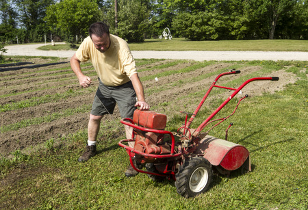 tine: A organic farmer trying to start a rear tine tiller. Stock Photo
