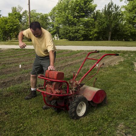tine: Organic farmer starting a older garden tiller. Stock Photo