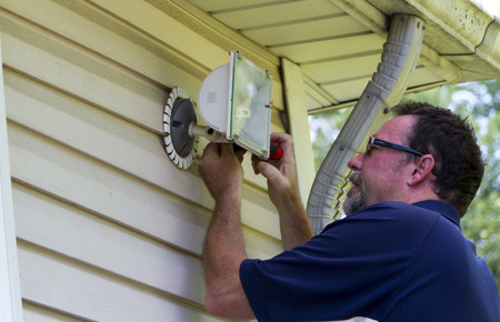 Electrician working on a outside light for a customer.