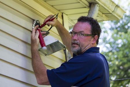 Electrician testing a outside light with a circuit tester.