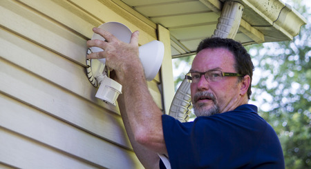 putting up: Electrician putting up a motion detector light for a customer.