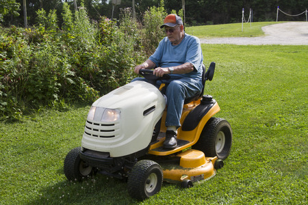 mowing grass: Older male mowing grass with his riding mower. Stock Photo