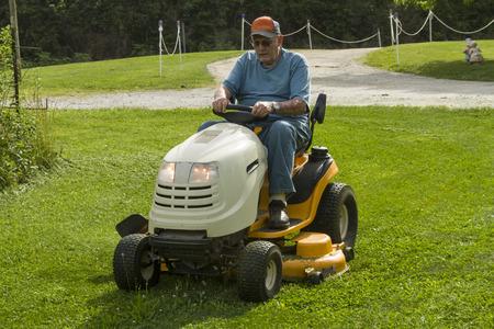 Older gentleman cutting grass on a riding lawnmower. Stock Photo