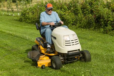 승마 잔디 깎는 기계에 잔디를 절단 오래된 신사. 스톡 콘텐츠