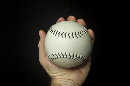 Game used white softball in hand.