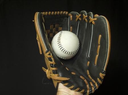 fastpitch: Softball mitt with white softball in webbing.