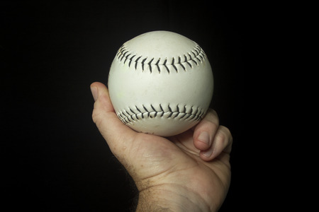 fastpitch: White softball in hand ready to throw. Stock Photo