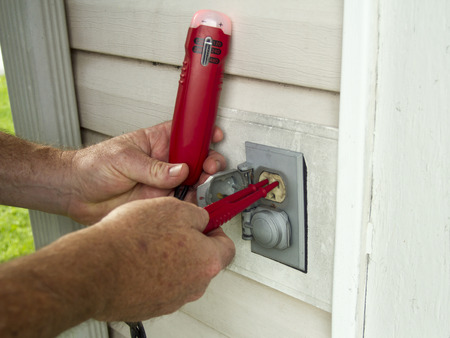 manual test equipment: ELectrician testing a outside electrical outlet on a older house.