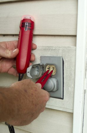 manual test equipment: Electrician testing a outside electrical outlet. Stock Photo