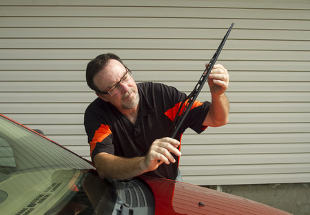 blades: Mechanic installing a new windshield wiper blade on a vehicle.