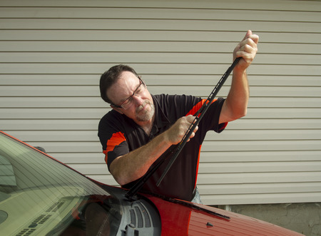 streaking: Mechanic changing windshield wiper blades on a car. Stock Photo