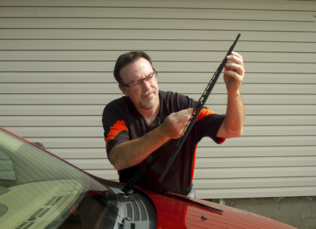 Mechanic changing windshield wipers on a crossover SUV. Foto de archivo