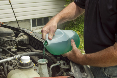 refilling: Mechanic refilling windshield wiper fluid in a customers car. Stock Photo