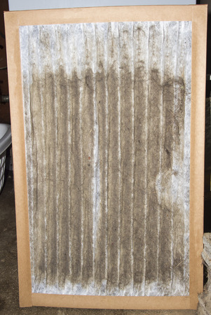 Front view of a dirty furnace filter taken out of a customers gas furnace. Stock Photo