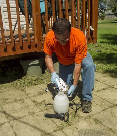 weeding: Worker poring weed killer into a sprayer.