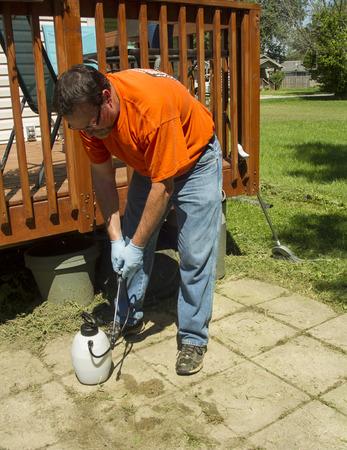 crop sprayer: Worker spraying weed killer on a customers patio.