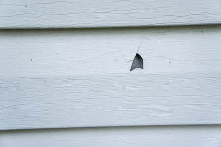 집의 비닐 사이딩에 우박 손상.