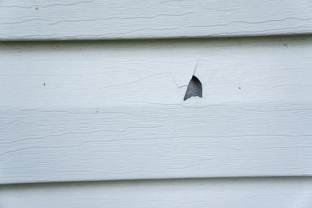 Hail damage on vinyl siding of a house.