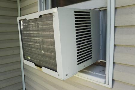 Venster lucht coniditoner unit wordt gebruikt tijdens de hoe zomerdagen voor comfort, Stockfoto