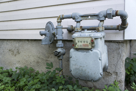 residential: Older residential  gas meter on the outside of a home. Stock Photo