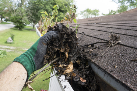 Worker cleaning gutters for a customer. Stock Photo - 44096716