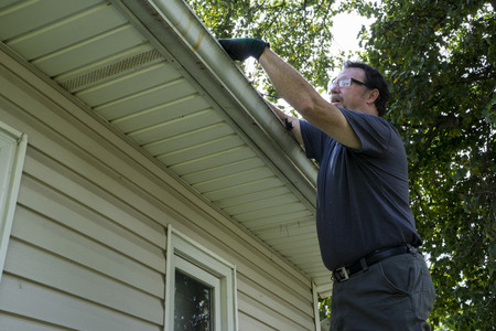 Cleaning gutters on a residential home. Stock Photo - 43716051