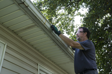old house window: Cleaning gutters of leaves and sticks on a home. Stock Photo