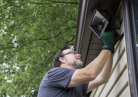 wirework: Electrician taking down a exterior light on a older home. Stock Photo