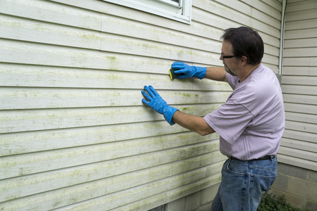 Contractor cleaning algae  and mold from vinyl siding of a customers home. Stock Photo