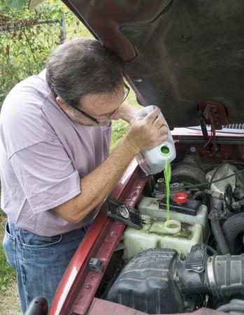 Mechanic adding engine coolant to customers vehicle.