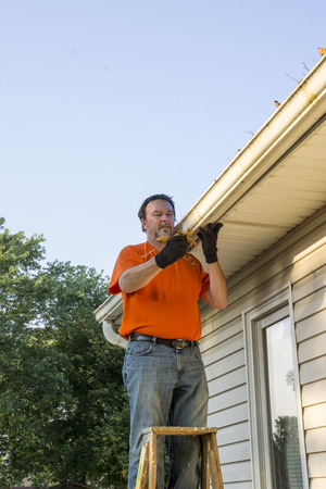 Homeowner cleaning dry leaves from his gutters on his home.