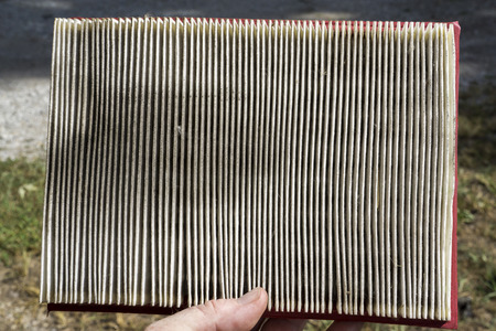 dirty car: Mechanic examing a dirty air filter taken from a customers car.