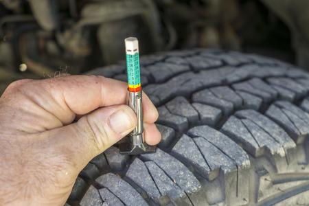 Using a tread wear gauge on a truck tire.
