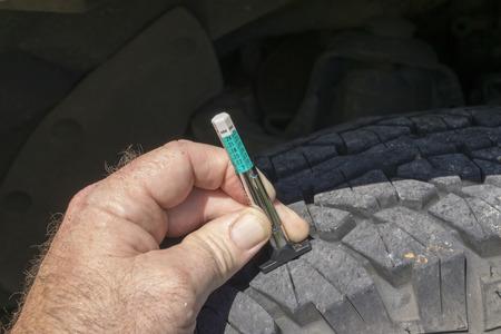 Measuring tread wear on a front truck tire.