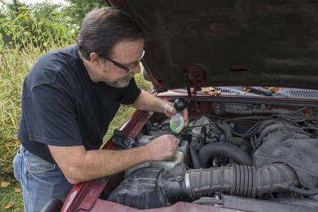 antifreeze: Mechanic testing antifreeze strength and levels in a customers truck.