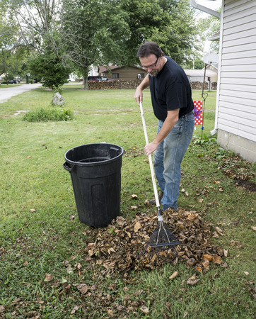 raking: Worker raking leaves in the front yard for a customer. Stock Photo